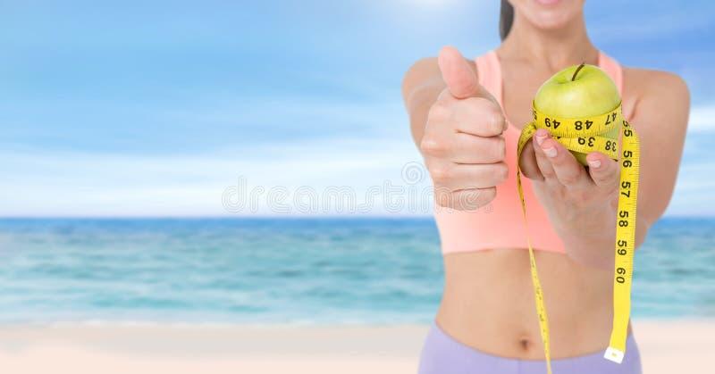 Peso de medición de la mujer con la cinta métrica en la cintura y la manzana el sostenerse en la playa del verano foto de archivo libre de regalías
