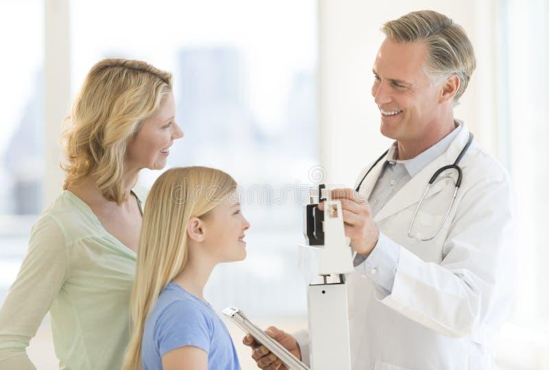 Peso del doctor Examining Girl mientras que mira a la mujer en clínica fotografía de archivo libre de regalías