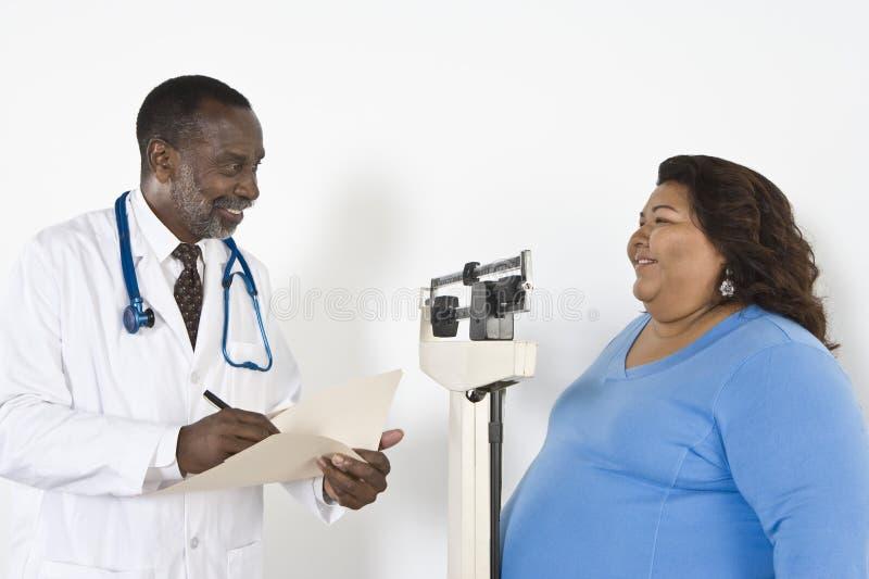 Peso do doutor Examining Patient foto de stock