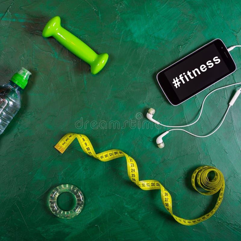 Peso, garrafa de água, smartphone, fones de ouvido e fita de medição no fundo verde Aptidão de Hashtag no smartphone imagens de stock royalty free