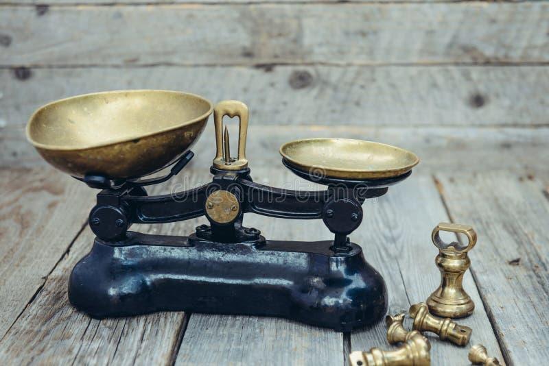 Pesos antiguos de la escala de medición del vintage con las bandejas de cobre amarillo en el fondo rústico de madera Foco selecti fotografía de archivo