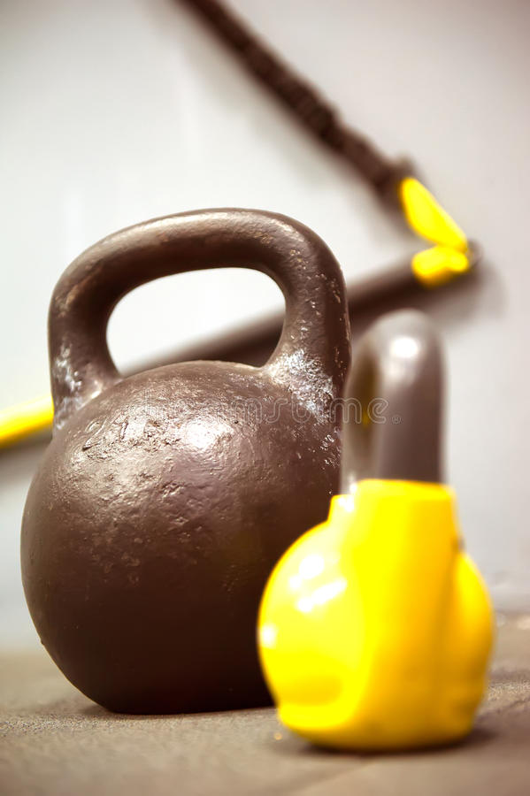 Pesos coloridos dos kettlebells no assoalho do gym - focalize o sino grande da chaleira fotografia de stock royalty free