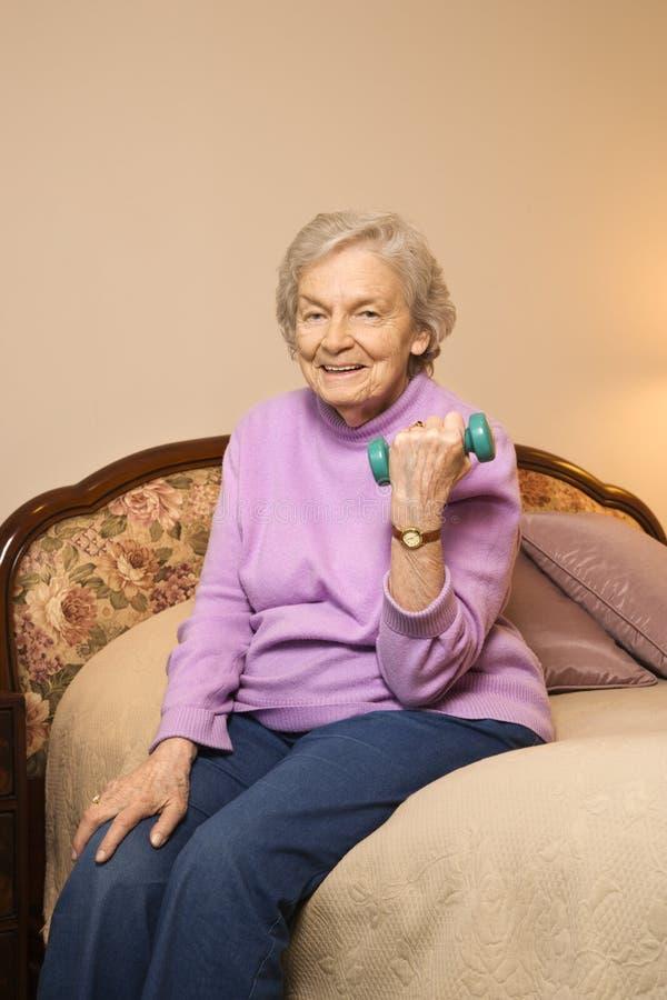Pesos de elevación de la mujer mayor. imagen de archivo libre de regalías