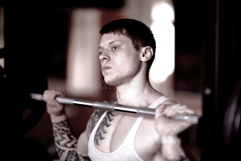 Pesos de elevación del hombre hermoso - un barbell - en un gimnasio imagen de archivo libre de regalías
