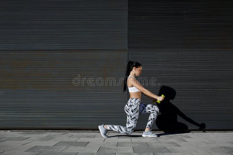 Pesos de elevación femeninos atléticos mientras que se resuelve contra la pared con el espacio de la copia para su mensaje de tex fotografía de archivo