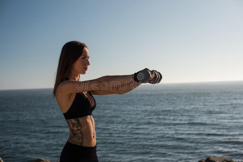Pesos de elevación de la mujer apta - al aire libre foto de archivo
