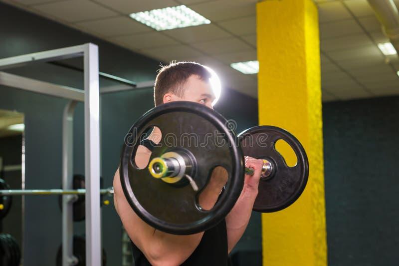 Pesos de elevación musculares del hombre joven en gimnasio fotos de archivo libres de regalías