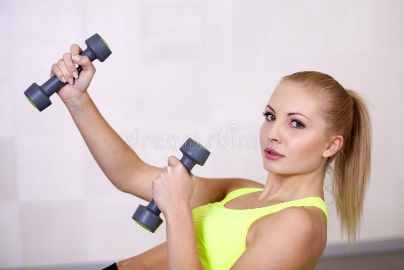 Pesos de levantamento da menina bonita ativa dos esportes que fazem o exercício em um clube ou em um gym de aptidão foto de stock royalty free