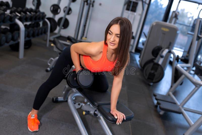 Pesos de levantamento da mulher apta consider?vel do retrato no banco no gym fotografia de stock royalty free
