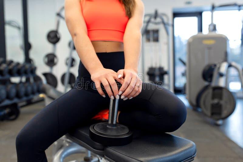 Pesos de levantamento da mulher apta consider?vel do retrato no banco no gym imagens de stock royalty free