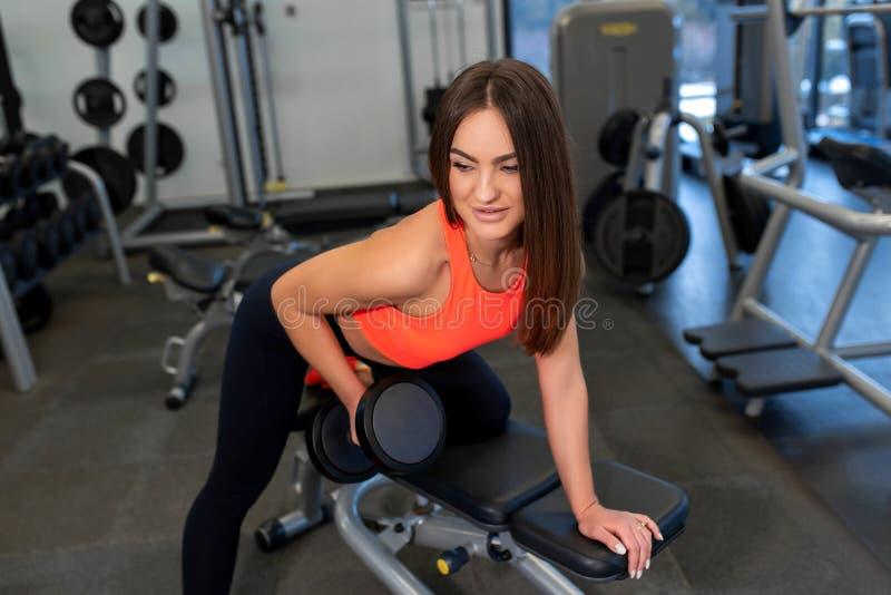 Pesos de levantamento da mulher apta consider?vel do retrato no banco no gym fotos de stock royalty free