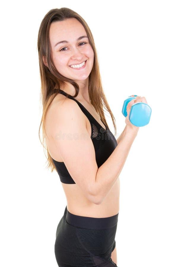 Pesos de levantamento da mulher bonita apta dos jovens no gym no fundo branco foto de stock