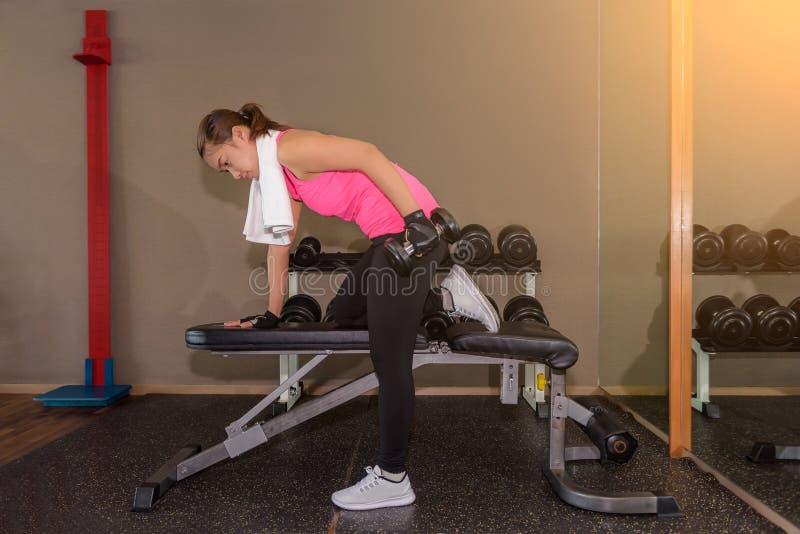 Pesos de levantamento do peso do treinamento da força da mulher do gym da aptidão dentro fotografia de stock royalty free