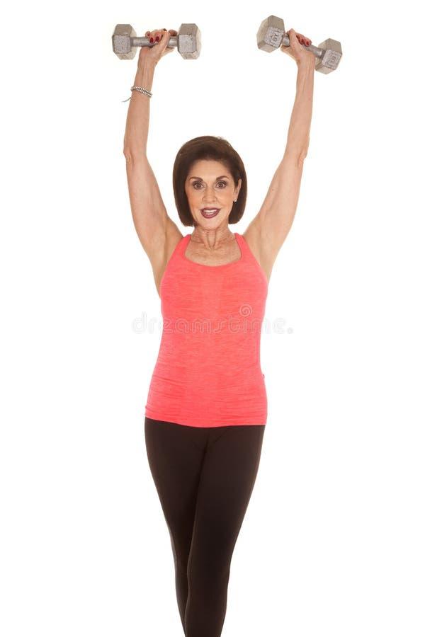 Pesos do exercício da mulher mais idosa acima da cabeça fotos de stock