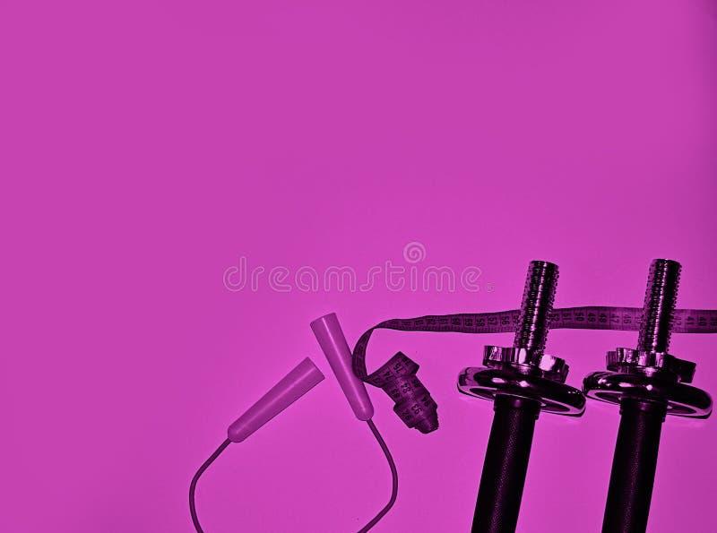 Pesos do ferro, corda de salto, néon de medição da fita, conceito roxo da aptidão da cor Material desportivo para o halterofilism imagens de stock