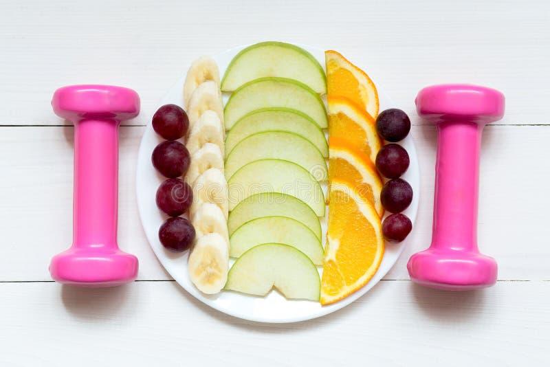 Pesos e frutos fêmeas na placa branca em um fundo de madeira branco foto de stock