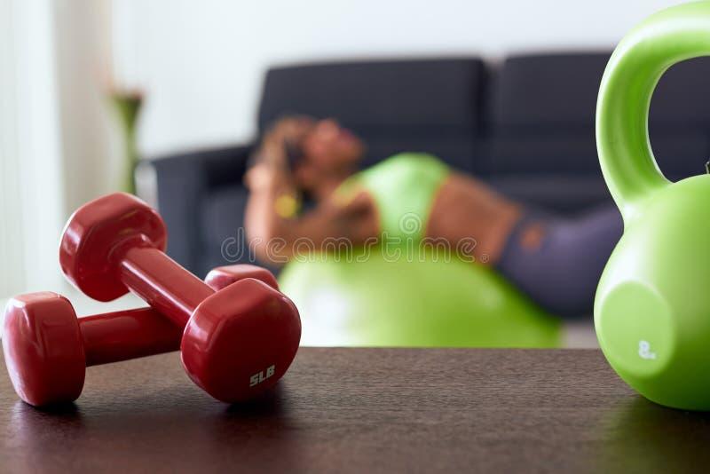 Pesos vermelhos da aptidão home em Abs do treinamento da tabela e da mulher fotografia de stock