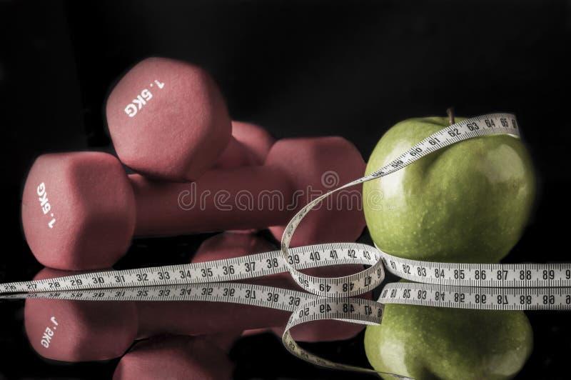 Pesos vermelhos e maçã cercados pela fita da medida no preto foto de stock
