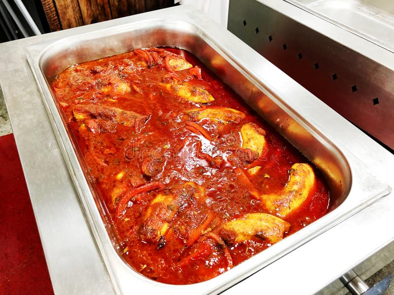 Pesque com a cebola das alcaparras cozida no macro do molho de tomate em um prato do cozimento fotografia de stock