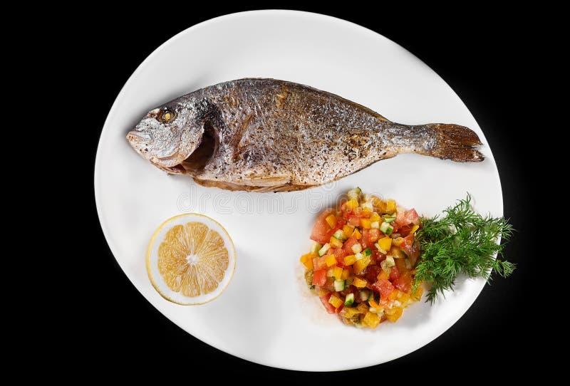 Pesque inteiro cozido prato da grade grelhado em uma placa com vegetais e limão na parte superior para o menu imagem de stock royalty free