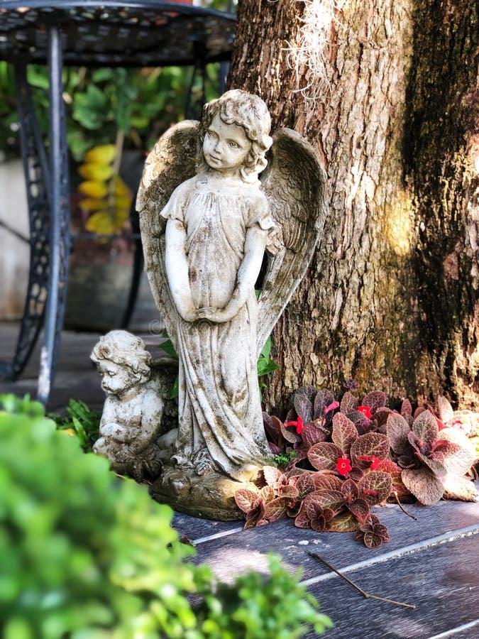 Pesque la estatua y el cupido con caña en el jardín, muestras del amor foto de archivo libre de regalías