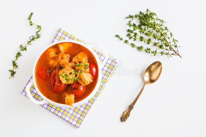 Pesque la sopa con bacalao, el tomate, la cebolla, el ajo y el tomillo en cuenco en la tabla blanca, visión superior imagen de archivo