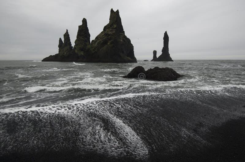 Pesque las rocas de los fingeres con cebo de cuchara del ` s en la playa de Vik imagen de archivo