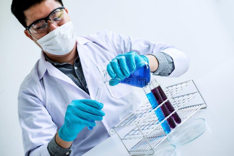 A pesquisa do laboratório da bioquímica, químico está analisando a amostra no laboratório com equipamento e produtos vidreiros da imagem de stock