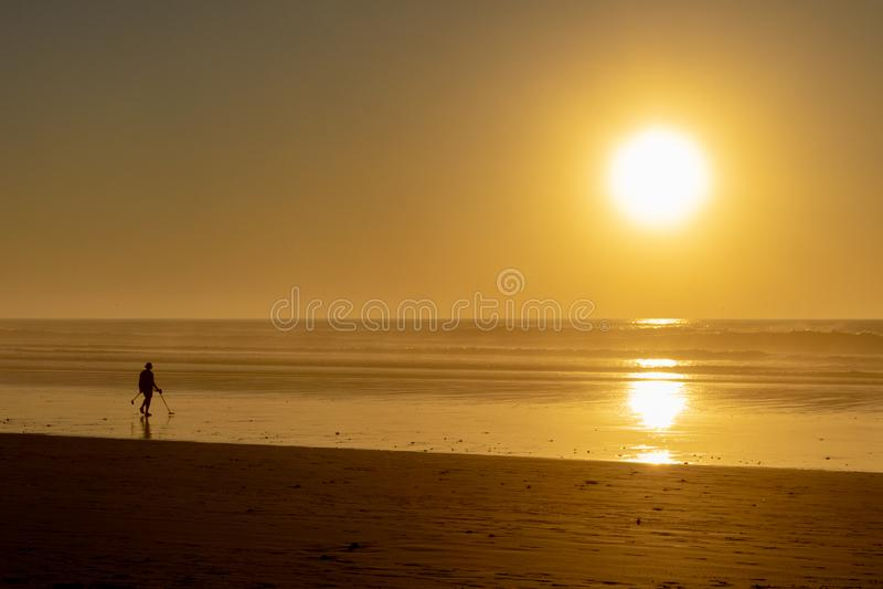 Pesquisa pelo tesouro metálico na maré baixa na praia no por do sol imagens de stock