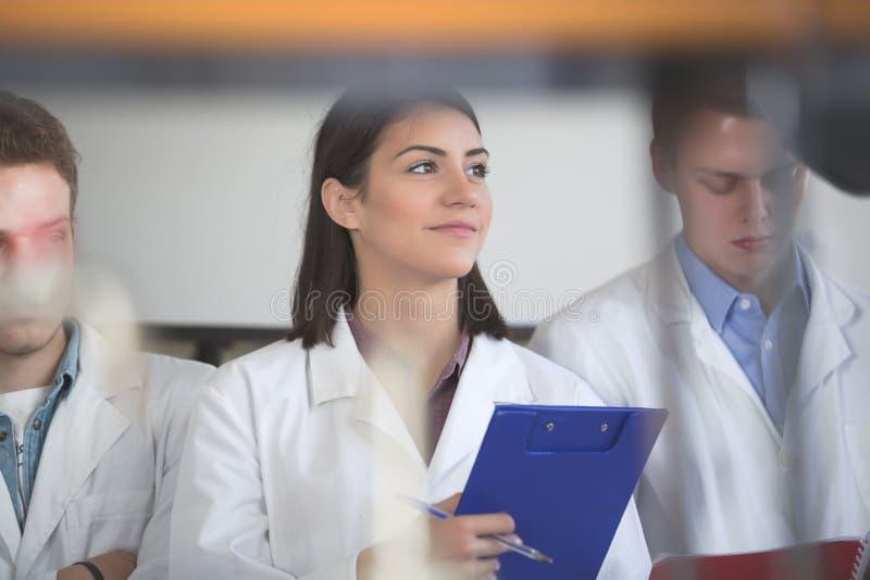 Pesquisador científico que guarda um dobrador da pesquisa química da experiência Estudantes da ciência que trabalham com produtos fotografia de stock