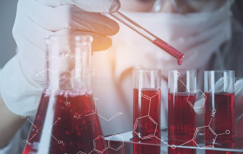 Pesquisador com os tubos de ensaio químicos do laboratório de vidro com líquido foto de stock royalty free