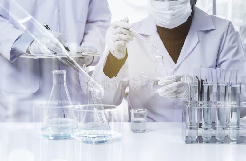 Pesquisador com os tubos de ensaio qu?micos do laborat?rio de vidro com l?quido para anal?tico, m?dico, farmac?utico e a pesquisa imagens de stock