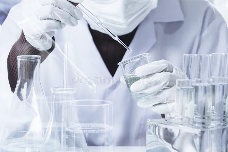 Pesquisador com os tubos de ensaio qu?micos do laborat?rio de vidro com l?quido para anal?tico, m?dico, farmac?utico e a pesquisa foto de stock