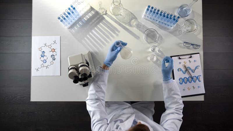 Pesquisador da bioquímica observando o agente químico na garrafa no laboratório, topview imagens de stock