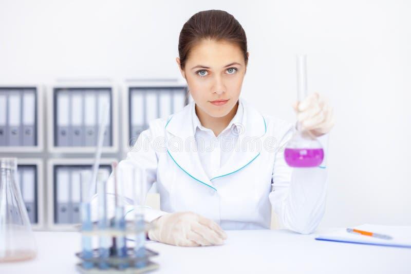Pesquisador fêmea químico novo que trabalha com produtos químicos no trabalho foto de stock