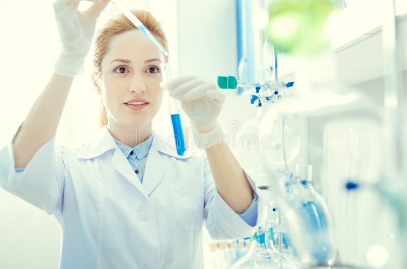 Pesquisador fêmea que mistura líquidos químicos no laboratório imagem de stock