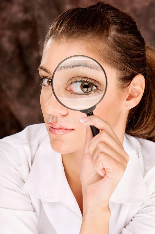 Pesquisador que olha através do vidro da lente de aumento imagem de stock