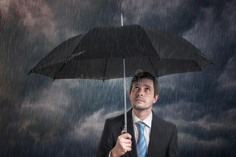 Pessimistic businessman with black umbrella in storm. Pessimistic businessman with black umbrella in storm royalty free stock images