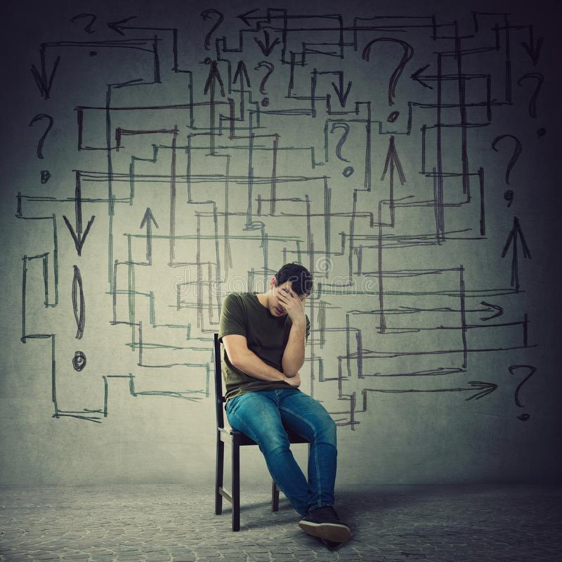Pessimistic, disappointed man sitting on a chair in a dark room covering face with hand. Desperate guy try to solve a questions. Maze and find the correct royalty free stock images