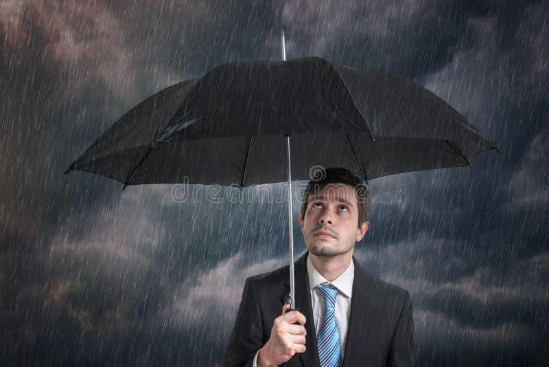 Pessimistischer Geschäftsmann mit schwarzem Regenschirm im Sturm lizenzfreie stockbilder