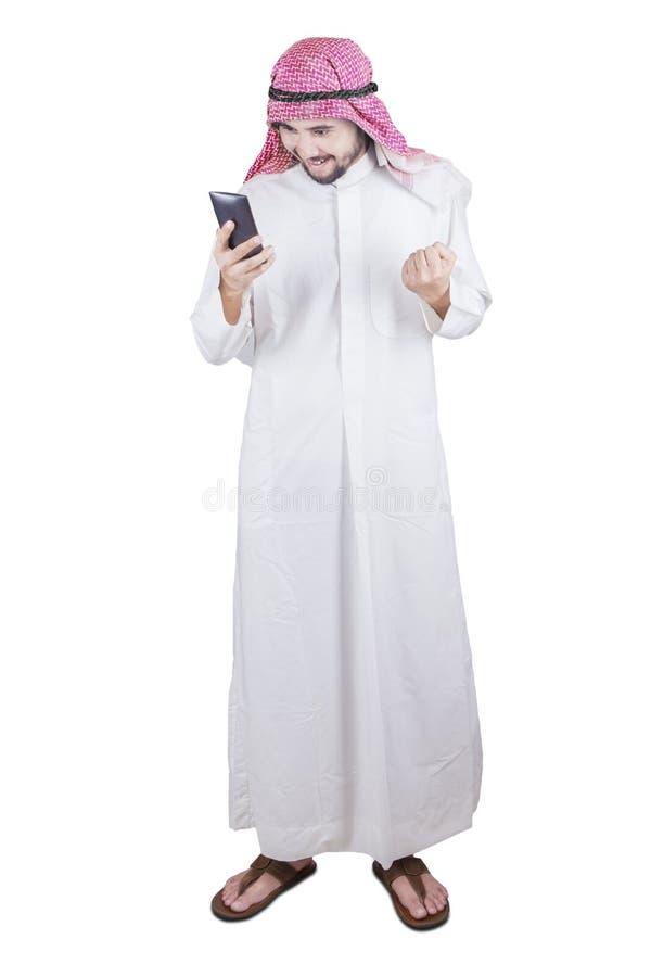 Pessoa árabe que olha o telefone celular no estúdio fotos de stock