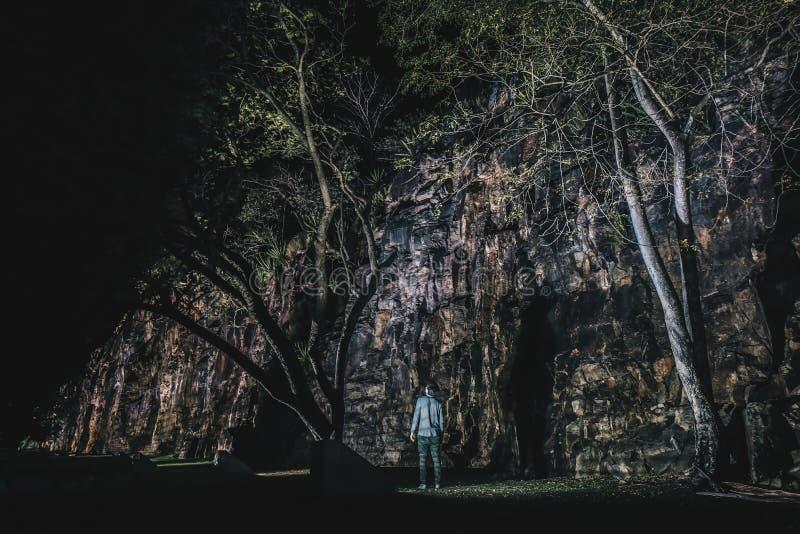 Pessoa anônima perto da caverna e das árvores foto de stock royalty free