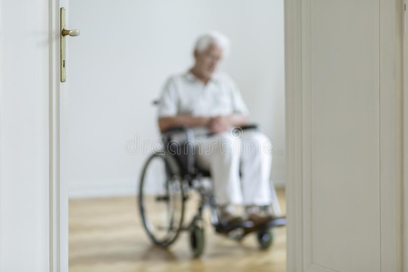 Pessoa borrada em uma cadeira de rodas no fundo apenas em casa foto de stock royalty free