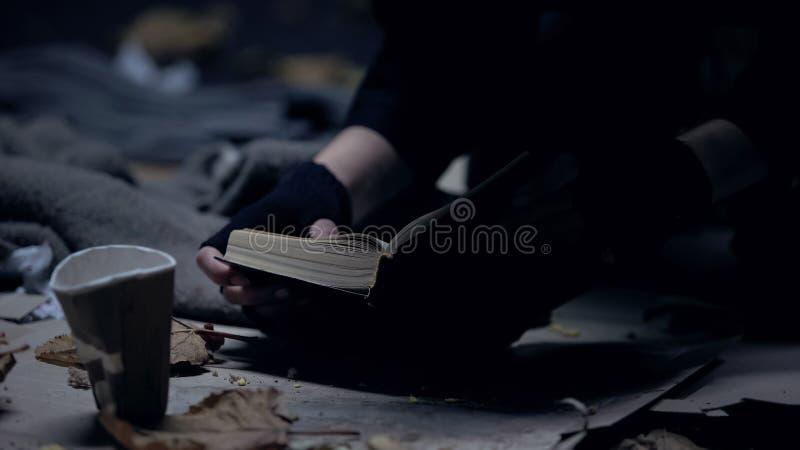 Pessoa desabrigada pobre que senta-se na Bíblia de leitura à terra, rezando para a melhor vida foto de stock