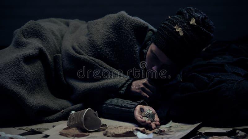 Pessoa desabrigada que encontra-se na rua e que conta as doações, dinheiro para o alimento, caridade imagem de stock royalty free