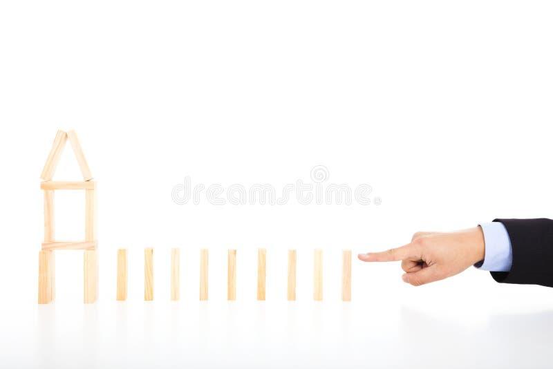 A pessoa do negócio pronta para empurrar dominós e a casa dão forma foto de stock