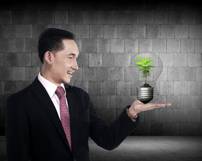 Pessoa do negócio que guarda a ampola com planta para dentro fotos de stock