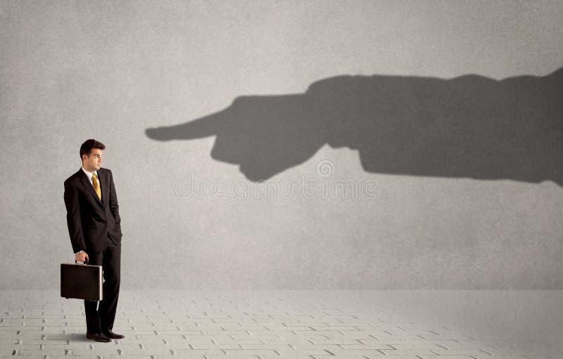 Pessoa do negócio que olha a mão enorme da sombra que aponta nele concentrado imagens de stock royalty free