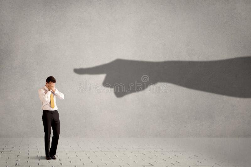 Pessoa do negócio que olha a mão enorme da sombra que aponta nele concentrado foto de stock royalty free
