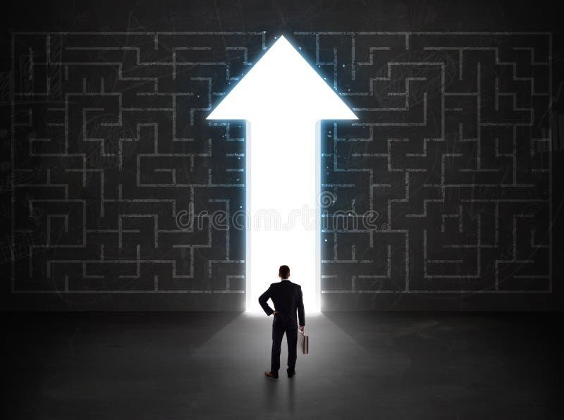 Pessoa do negócio que olha o labirinto com a seta da solução na parede fotos de stock